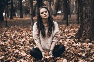 Girl in woodland sitting on leaves in despair